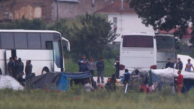 Migrants seen getting on coaches to leave Idomeni, on 24 May 2016