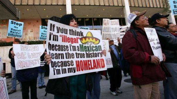 Mujer con cartel en contra de las deportaciones