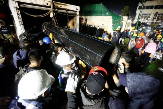 Rescatistas y voluntarios transportan un tubo en las inmediaciones del Colegio Enrique Rébsamen, del barrio Coapa, en el sureste de la Ciudad de México, parcialmente derrumbado por el terremoto de magnitud 7,1 que sacudió el país el martes.
