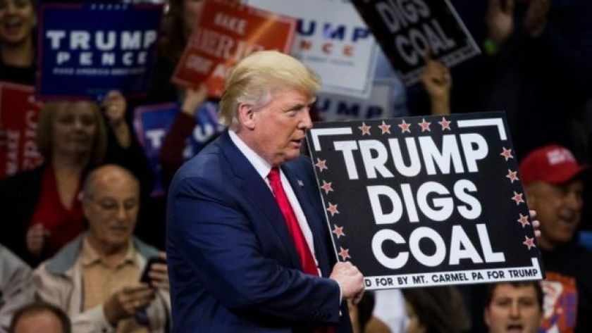 Republican presidential nominee Donald Trump holds a sign supporting coal during a rally at Mohegan Sun Arena in Wilkes-Barre, Pennsylvania (10 October 2016)