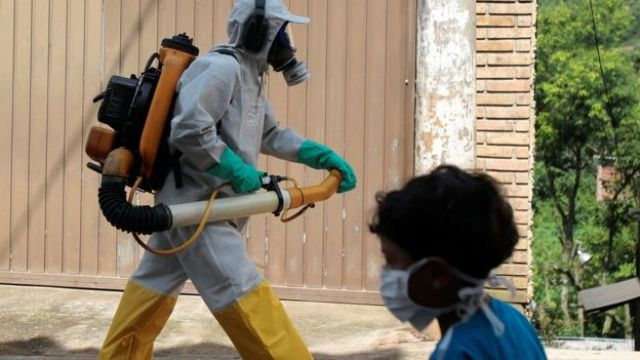 Agente de controle de vetores e menino com máscara se cruzam em São Paulo