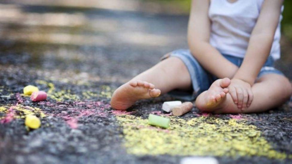 Niña sentada en la calle