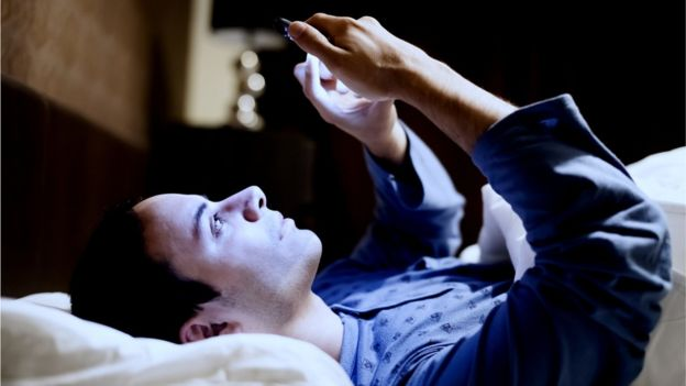 Man in bed using phone