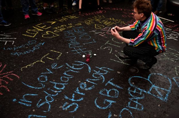A woman kneels amongst graffiti during a vigil in memory of the victims of the gay nightclub mass shooting