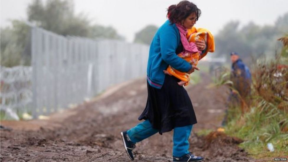 Migrant carrying a baby crosses the border near Roszke, 11 September 2015