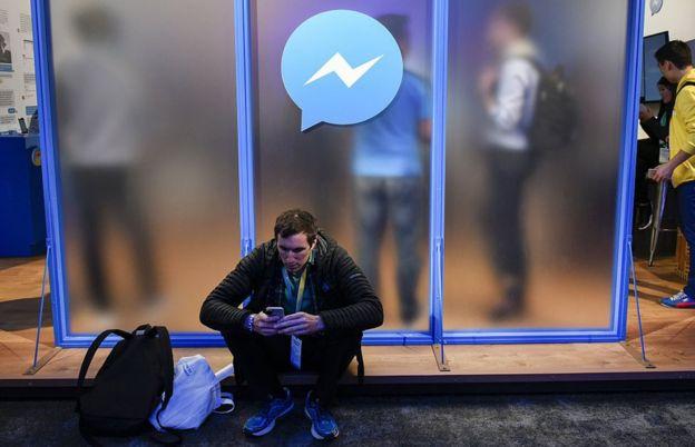 Un hombre con su celular sentado bajo el logo de Facebook Messenger.