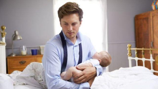 Hombre cargando a un bebé