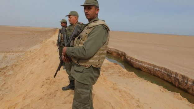 Tunisian soldiers stand on a sandbank during a presentation of the anti-jihadi fence, near Ben Guerdane, eastern Tunisia