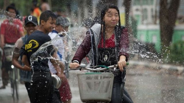A girl cycles past revellers throwing water at passersby during celebrations marking the beginning of the Buddhist New Year