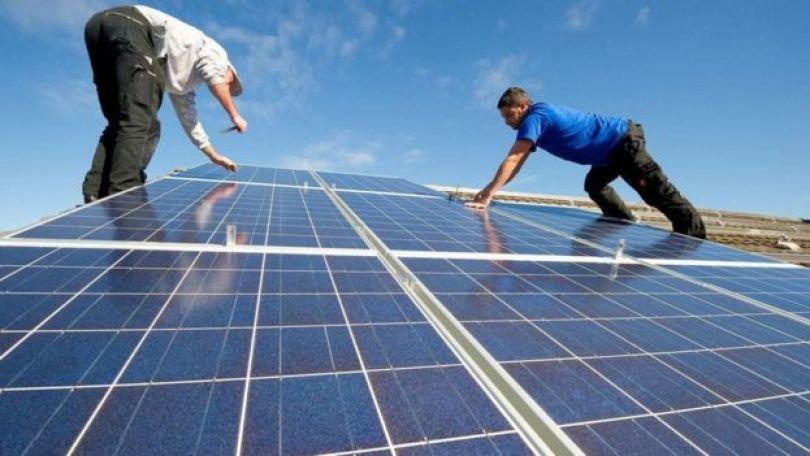Dois homens instalando painéis de energia solar