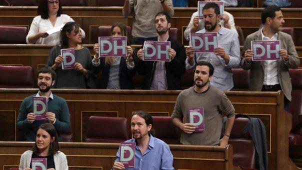 Parlamentarios con carteles con las letras DH piden respeto a los derechos humanos en el parlamento en Madrid