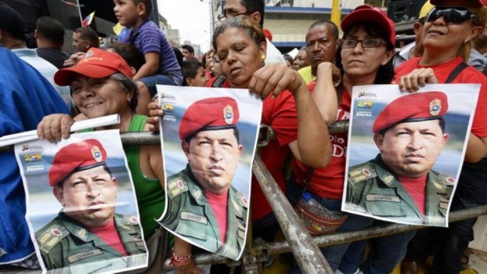 Supporters of President Nicolás Maduro hold posters of former President Hugo Chávez during a demonstration in Caracas on August 3, 2013.