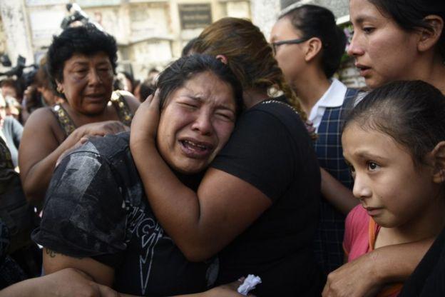 Mujer llora en los brazos de otra mujer