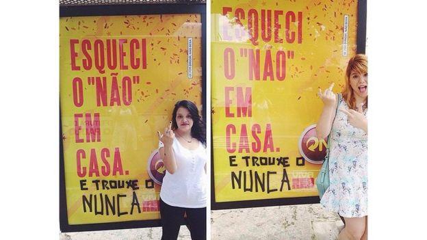 Ativistas posam em frente a cartaz