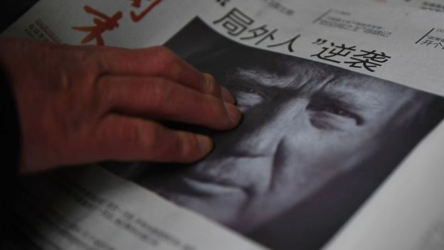 This file photo taken on November 10, 2016 shows a man buying a newspaper featuring a photo of US President-elect Donald Trump