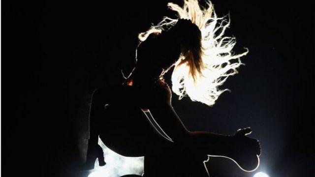 Contraluz de Beyonce en medio de un concierto. Su cabello se agita al viento.