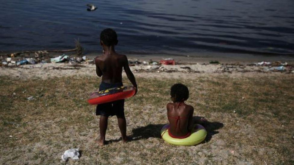 Crianças olham para a Baía de Guanabara