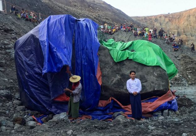 A man poses for photographs next to a worker preparing to cover the giant jade stone as miners gather and watch at a mine in Phakant, Kachin State, northern Myanmar