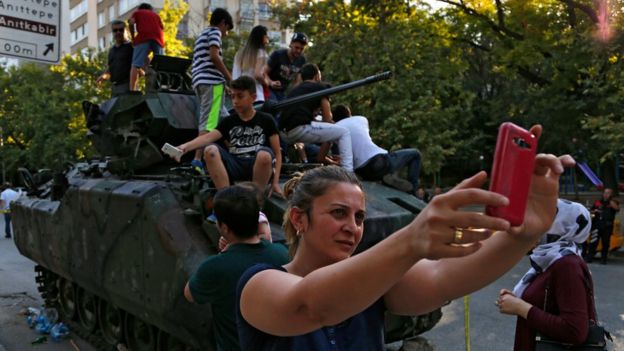 A woman takes a selfie in front a damaged Turkish military APC in Ankara on 16 July, 2016