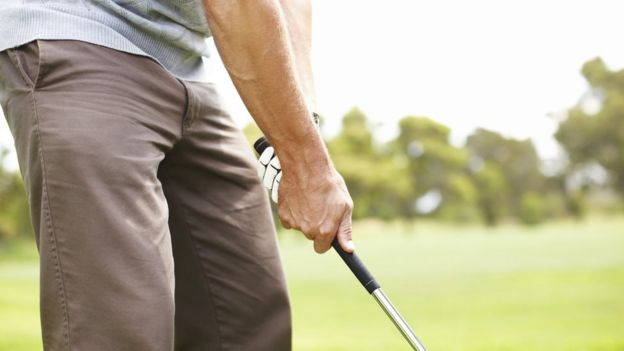 Homem que prende o clube de golfe
