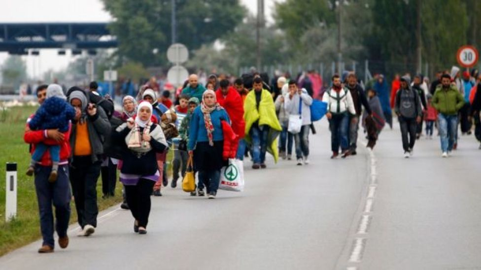 Migrants walk across the border at Nickelsdorf, Austria, 11 September 2011