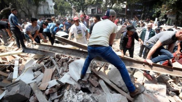 People remove debris of a building which collapsed after a quake rattled Mexico City