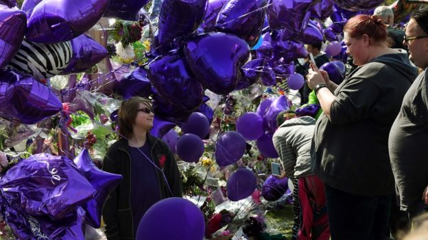 Prince fans pose for photos amongst a sea of purple balloons outside the Paisley Park compound in Minneapolis