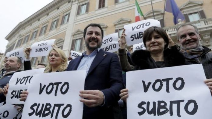 Northern League leader Matteo Salvini (C), holds a placard that reads