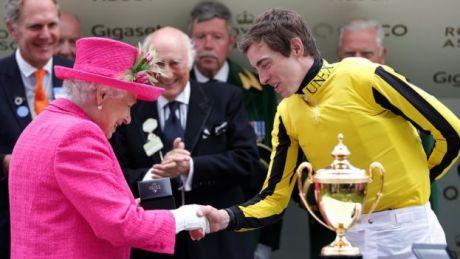 La reina estrechando la mano del jinete James Doyle.