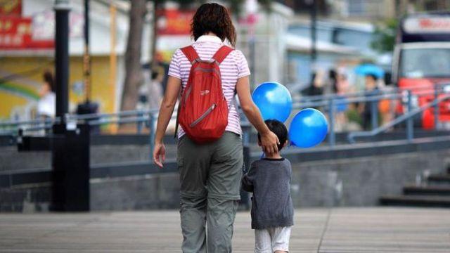 Mujer y niño caminando en la calle.