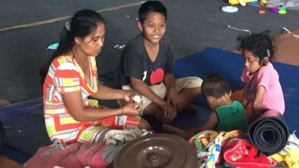 Ketut Seri and her young family are pictured sitting on the floor of a center