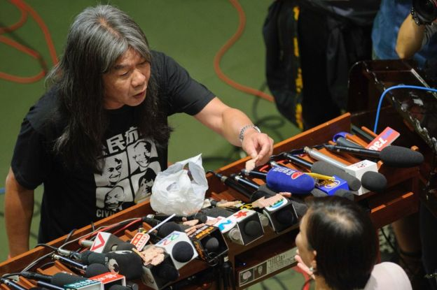 Pro-independence lawmaker Leung Kwok-hung (L), known as Long Hair, holds up a piece of lunchmeat as he argues with pro-Beijing lawmaker Priscilla Leung Mei-fun on 19 October 2016
