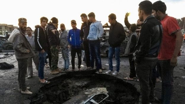 Locals look at debris at the scene of a massive car bomb in southern Baghdad(16 February 2017)
