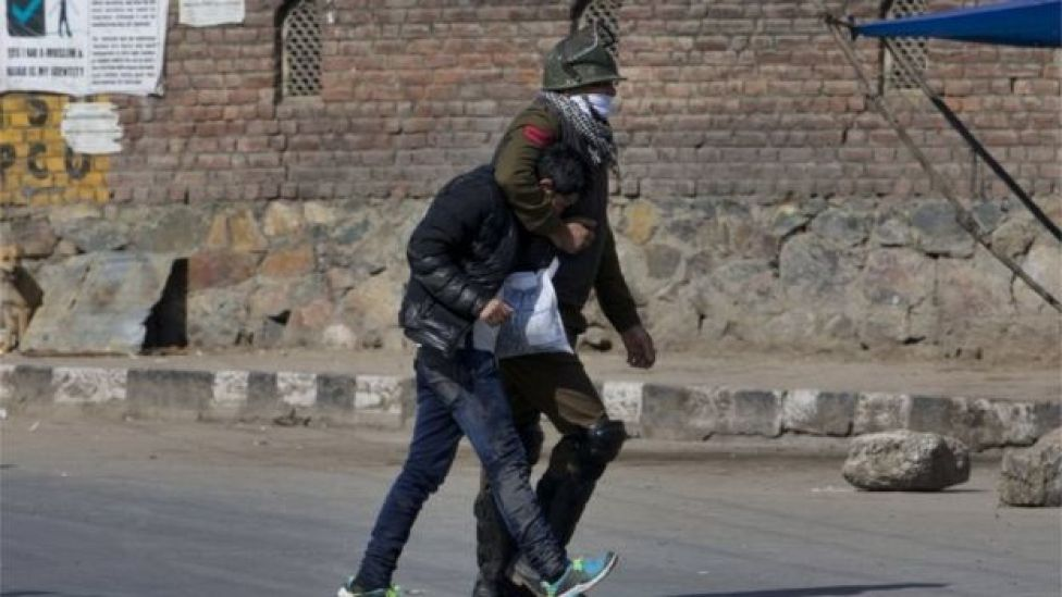 An Indian policeman detains a Kashmiri Muslim youth caught taking photographs with his cellphone during a protest in Srinagar, Indian controlled Kashmir, Friday, Feb. 26, 2016.