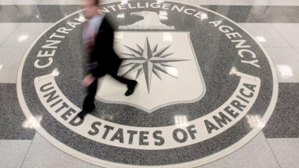 Un hombre camina encima de un logo de la CIA