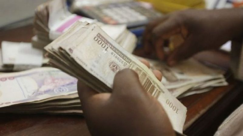 a money changer counts Nigerian Naira currency