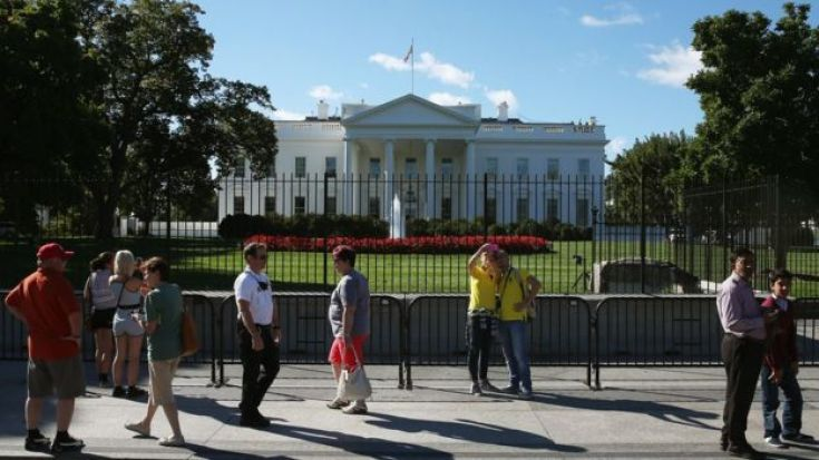 Tourists mill outside the north fence of the White House