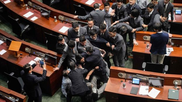 Newly elected lawmaker Baggio Leung (C, wearing glasses) is restrained by security after attempting to read out his Legislative Council oath at Legco in Hong Kong on November 2, 2016