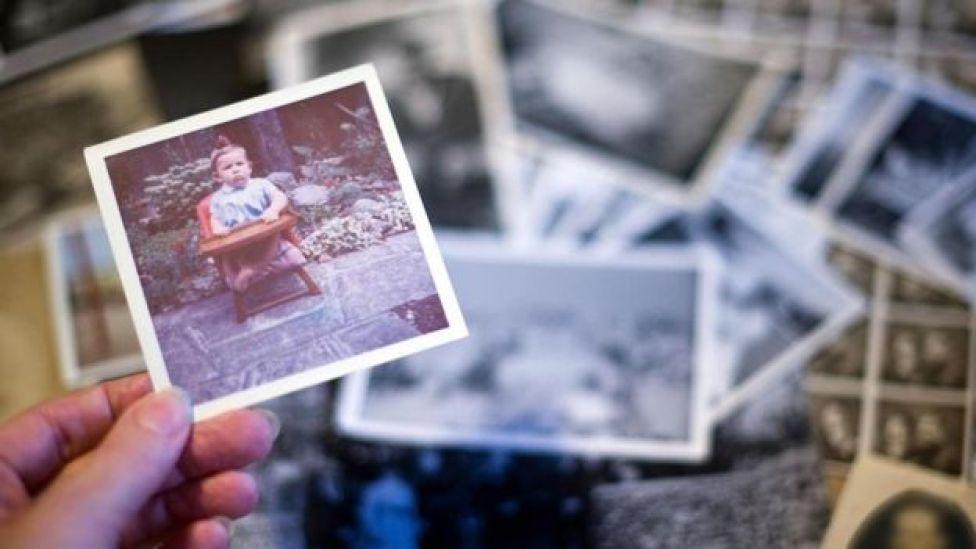 Una persona sosteniendo una fotografía en la mano, de una pila en una mesa