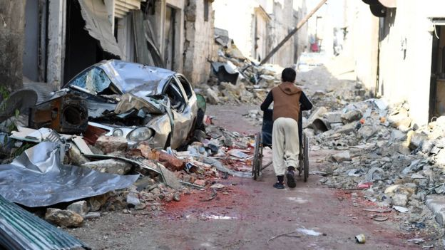A boy pushes a wheelchair along a damaged street in the east Aleppo neighborhood of al-Mashatiyeh, Syria, in this handout picture provided by UNHCR on January 4, 2017.