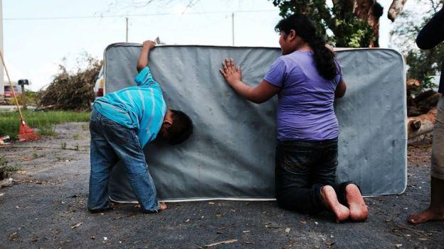 Crianças limpam colchão sujo após inundação