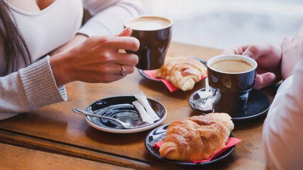 Duas pessoas bebeno café e comendo croissants