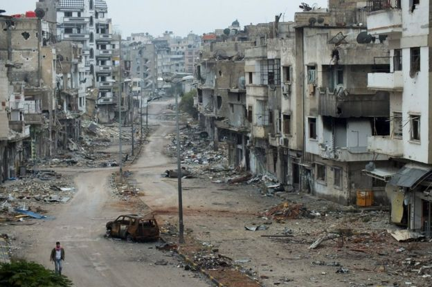 A man walks past damaged buildings along a street at the Khalidiya district of Homs, Syria (19 November 2012)