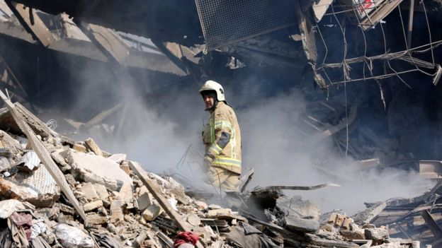 A rescue worker stand in the rubble of the collapsed Plasco building in Tehran, Iran (19 January 2017)
