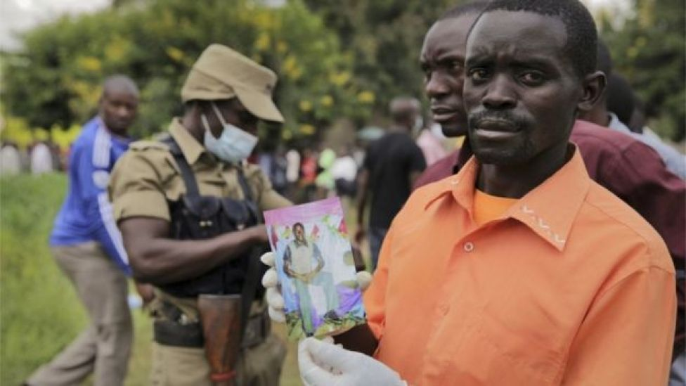 A man holding a picture of his relative.