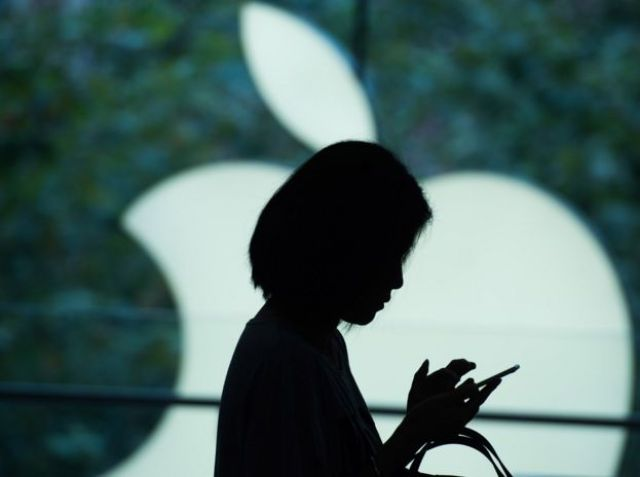 Mujer mira un teléfono delante de un logo de Apple