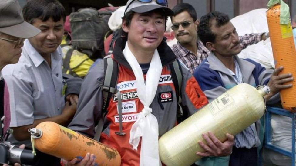 Leader of Everest clean up expedition Japanese mountaineer Ken Noguchi (C) holds empty oxygen bottles in Kathmandu airport, 23 May 2003