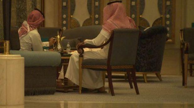 Saudimen in traditional dress sit in chairs in the Ritz Carlton in Riyadh, drinking coffee.