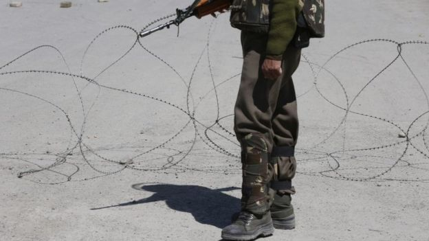 An Indian Paramilitary soldier stands guard near a barbed wire set up as a barricade during restrictions in Maisuma area of Srinagar on 14 April 2016
