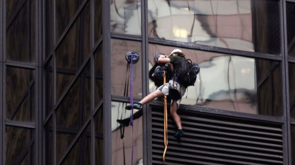 A man scales the all-glass facade of Trump Tower, Wednesday